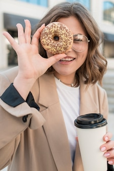 Portrait of young girl holding tasty doughnut