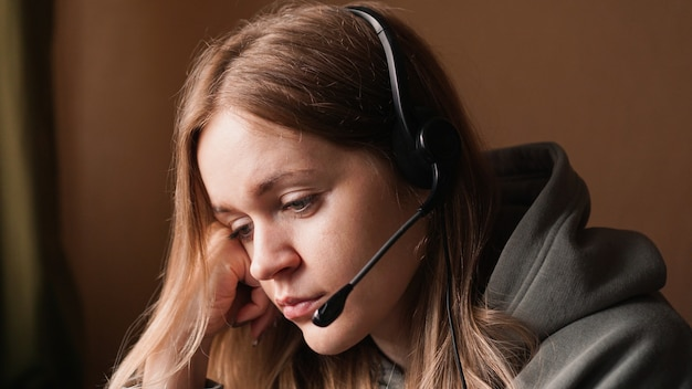 Portrait of young girl in a hoodie and with a headset tired call center worker