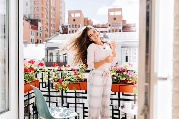晴れた朝に市のバルコニーに移動するパジャマの肖像少女。彼女の長い髪は風になびいていて、笑っています。