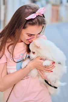 Portrait of a young girl kissing her white fluffy pomeranian dog.