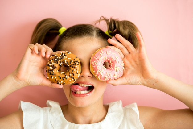 Portrait of young girl looking through two pink donuts, pink background,