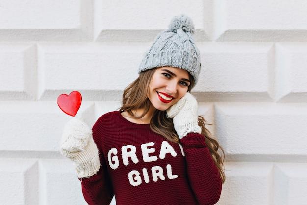 Ritratto giovane ragazza in marsala maglione e cappello lavorato a maglia sul muro grigio all'esterno. indossa guanti bianchi, tiene lecca-lecca cuore rosso e sorridente.
