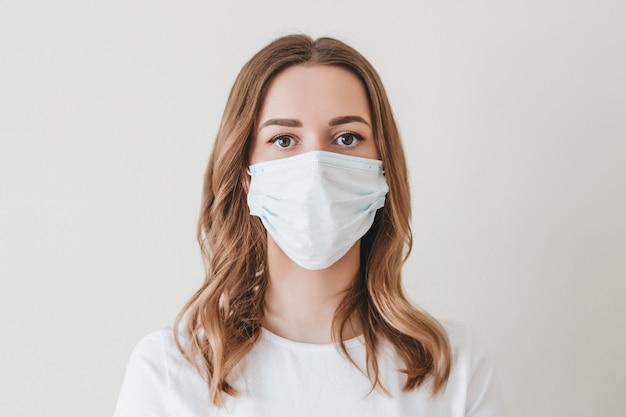 Portrait of a young girl in a medical mask isolated on a white wall wall. young woman patient