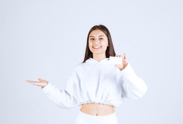 Ritratto di un modello di giovane ragazza con una carta su sfondo bianco-grigio.