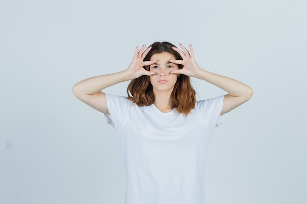 Portrait of young girl opening eyes with fingers in white t-shirt and looking sensible front view