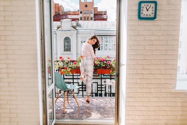 Ragazza del ritratto in portapigiama in movimento sul balcone in città nella mattina di sole. i suoi lunghi capelli volano al vento, sorride.
