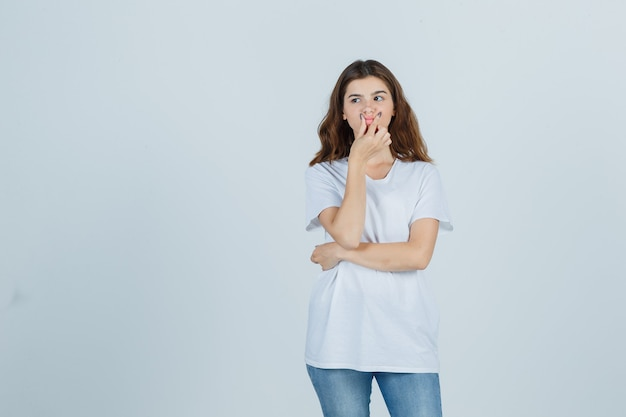Portrait of young girl pinching lips in white t-shirt, jeans and looking thoughtful front view