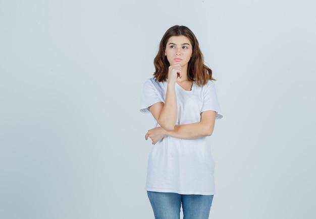 Ritratto di giovane ragazza appoggiando il mento a portata di mano in t-shirt bianca e guardando pensieroso vista frontale
