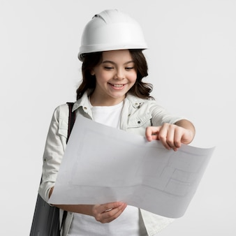 Portrait of young girl reading construction plan