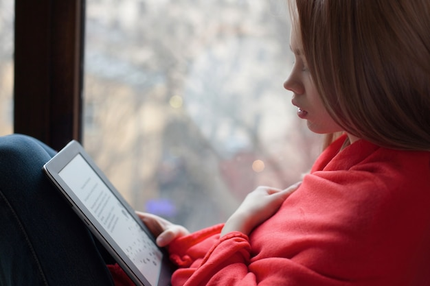 Portrait of a young girl reading an e-book.