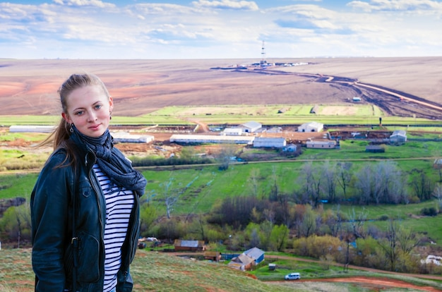 Portrait of a young girl on the rural landscape with drilling rigs in the field