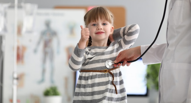 Portrait of young girl standing in modern office of professional therapist and showing approving gesture