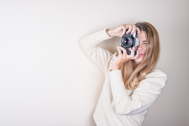 Portrait of a young girl taking pictures with a professional camera