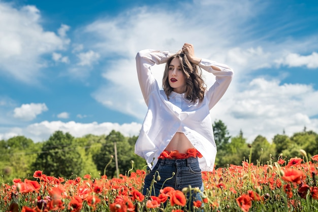Portrait of  young girl walking in poppy field at summer time. enjoy nature