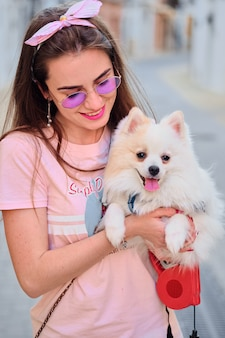 Portrait of a young girl walking with a white fluffy pomeranian.