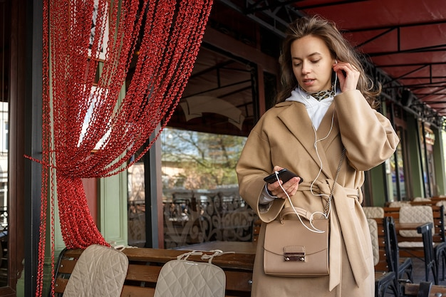 Portrait of young girl wearing coat listening for the music on cafe veranda with earphones holding cell phone in hands
