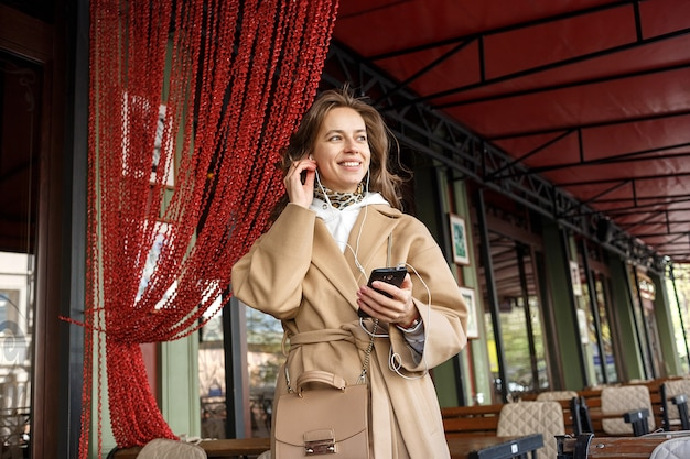 Portrait of young girl wearing coat listening to the music on cafe veranda with earphones holding cell phone in hands