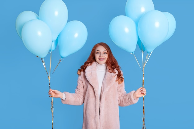Portrait of young girl wearing pale pink fur coat, holding birthday balloons for party, having red hair