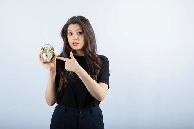 Portrait of young girl with alarm clock standing on grey.