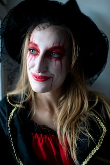 Portrait of a young girl with blond hair as a witch with bright make-up and leaking lipstick mysteriously looks to the side.