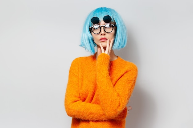 Portrait of young girl with blue hair in orange sweater, wearing round sunglasses on white background.