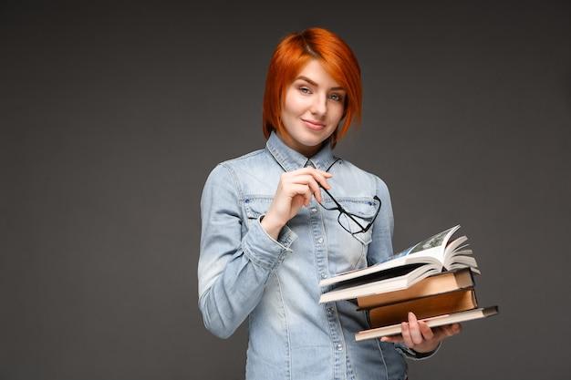 Ritratto di giovane ragazza con libri su sfondo grigio. copia spa