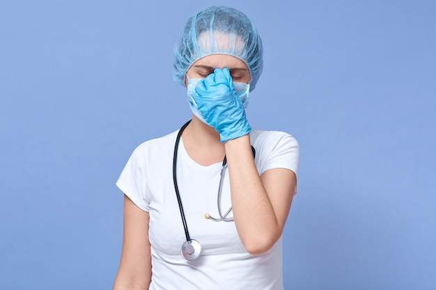 Portrait of young girl with closed eyes, having headache, holding hands on her forehead, wearing medical flu mask, disposable hat, has stethoscope around neck