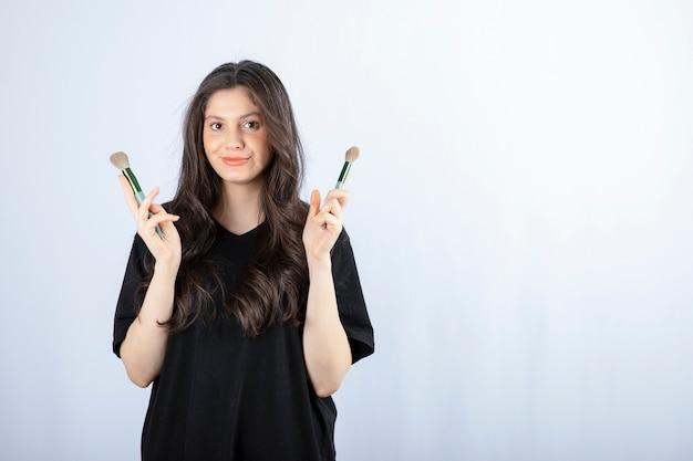 Ritratto di giovane ragazza con spazzole cosmetiche che guarda l'obbiettivo su bianco.
