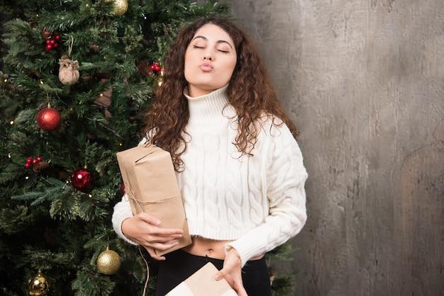 Ritratto di giovane ragazza con i capelli ricci che tiene due regali in un involucro
