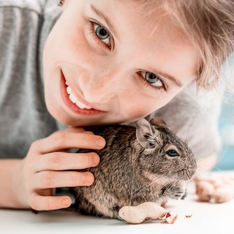 Portrait of young girl with degu squirrel