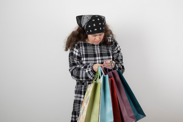 Portrait of young girl with down syndrome looking at bunch of shopping bag.