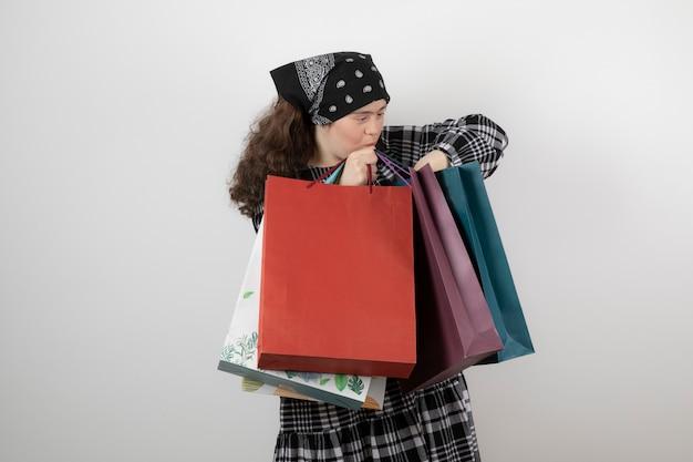 Ritratto di giovane ragazza con sindrome di down guardando il mazzo di shopping bag.