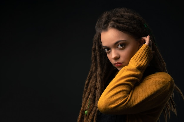 Portrait of a young girl with dreads on black