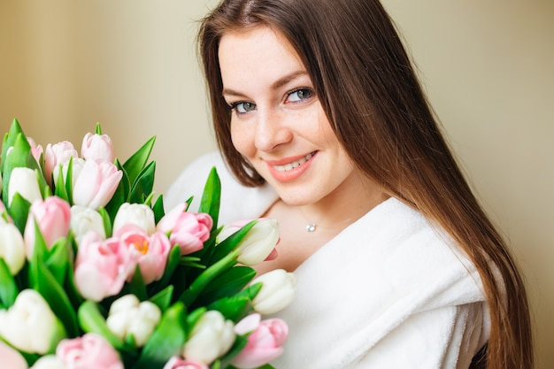 Portrait young girl with green eyes and long hair holds big bouquet of tulips in hands looking at camera.