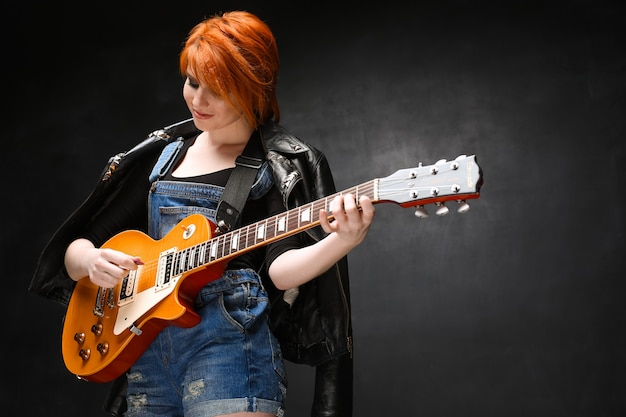 Portrait of young girl with guitar over black background.