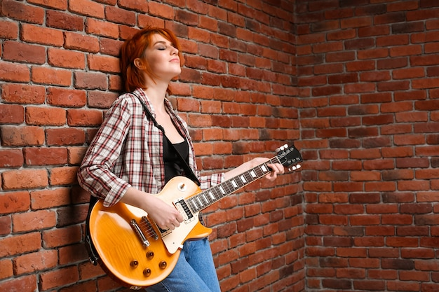 Portrait of young girl with guitar over brick background.