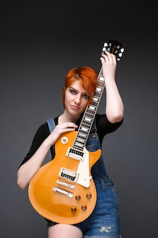 Portrait of young girl with guitar over grey background.