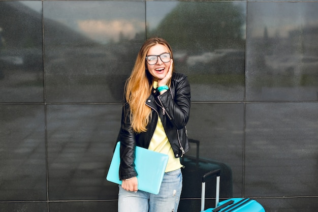 Portrait of young girl with long hair in glasses is standing outside on black background. she wears black jacket with jeans and holds laptop. she is smiling to the camera.