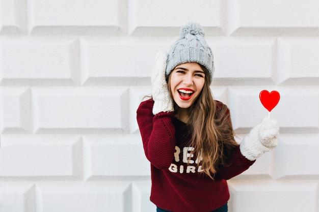 Ragazza del ritratto con capelli lunghi in cappello lavorato a maglia e maglione marsala con lecca-lecca cuore rosso sul muro grigio. indossa guanti bianchi caldi, ridendo.