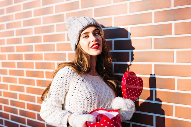 Portrait young girl with long hair in knitted hat, warm sweater and gloves on wall  outside. she holds open box heart in hands, smiling .
