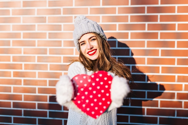 Portrait young girl with long hair in knitted hat, warm sweater on wall  outside. she stretching red heart in gloves .