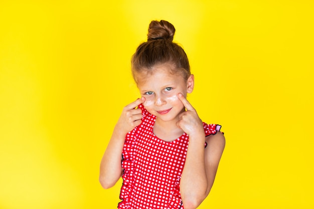 Portrait of young girl with sun protection cream on her face. yellow background