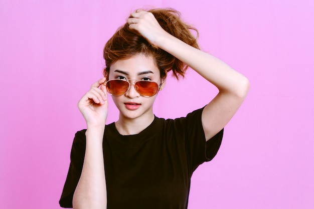 Portrait of young girl with sunglasses on pink background