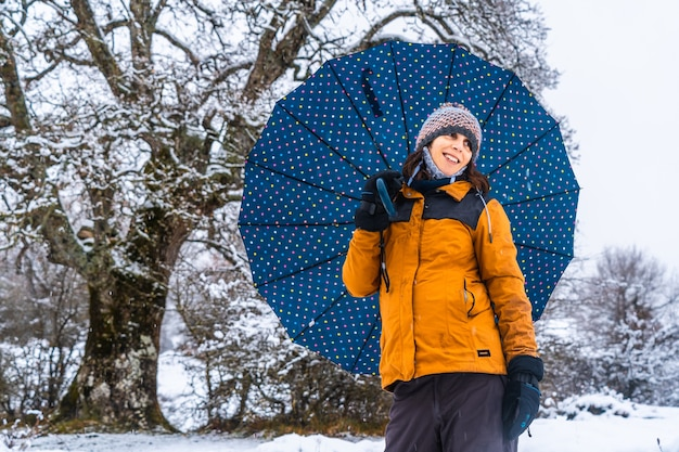 Portrait of a young girl with a yellow jacket and an umbrella next to a giant snowy tree. snow in the town of opakua near vitoria in araba