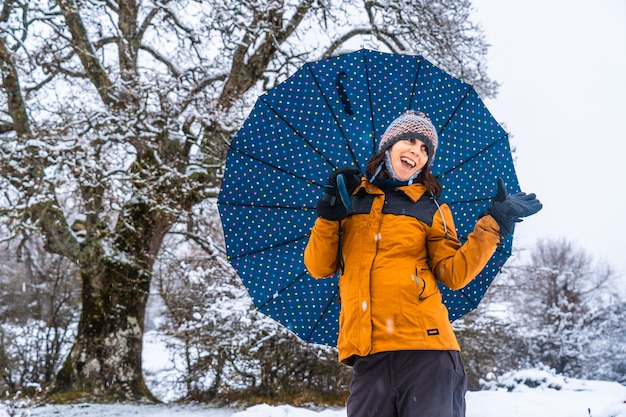 Portrait of a young girl with a yellow jacket and an umbrella next to a giant snowy tree. snow in the town of opakua near vitoria