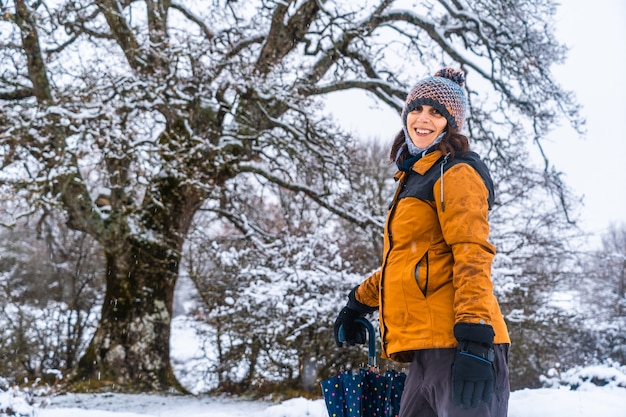 Portrait of a young girl in a yellow jacket next to a giant snowy tree. snow in the town of opakua near vitoria in araba
