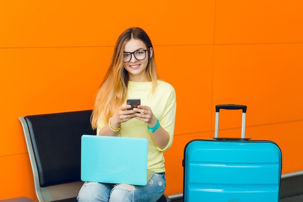 Portrait of young girl in yellow sweater sitting on chair on orange background. she has blue laptop on knees and blue suitcase near. she is smiling to the camera.