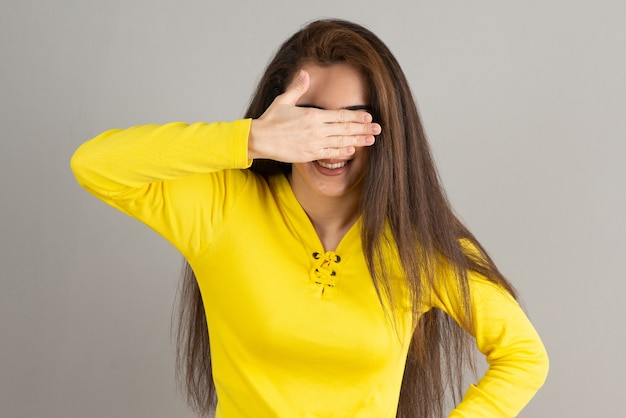 Portrait of young girl in yellow top covering her face on gray wall.
