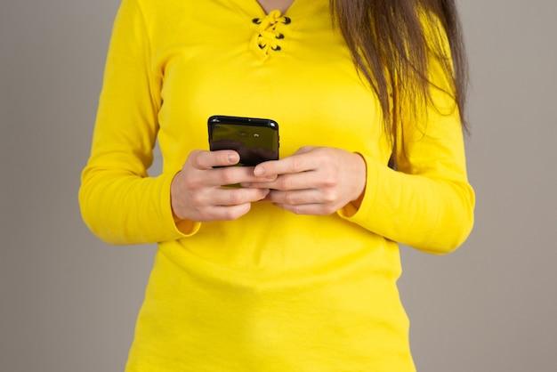 Ritratto di giovane ragazza in messaggistica superiore gialla con il cellulare sul muro grigio.