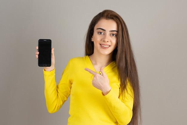 Ritratto di giovane ragazza in giallo top in posa con il cellulare sul muro grigio.